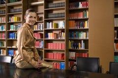 Donna sorridente che si siede sullo scrittorio delle biblioteche Immagini Stock