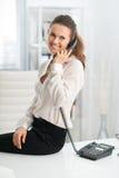 Donna sorridente che si siede sullo scrittorio e che parla sul telefono immagini stock