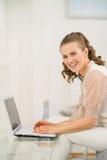 Donna sorridente che si siede sullo strato in salone e nel per mezzo del computer portatile Fotografia Stock Libera da Diritti