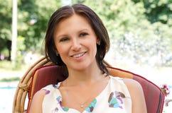 Donna sorridente che si siede in una presidenza di giardino Fotografie Stock