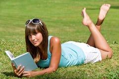 Donna sorridente che si trova giù sull'erba con il libro immagini stock
