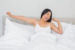 Donna sorridente che si trova a letto allungando di mattina Immagine Stock Libera da Diritti
