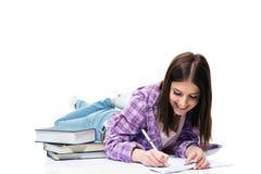 Donna sorridente che si trova sul pavimento e che scrive in taccuino Fotografia Stock Libera da Diritti