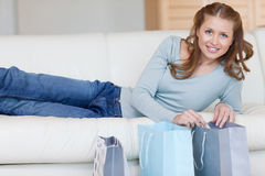 Donna sorridente che si trova sul sofà accanto al suo acquisto Fotografie Stock Libere da Diritti