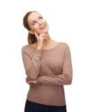 Donna sorridente che sogna sopra il fondo bianco Fotografia Stock