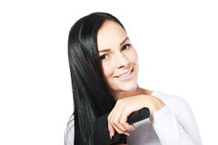 Donna sorridente che spazzola i suoi capelli fotografia stock libera da diritti