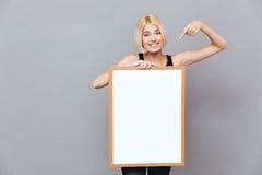 Donna sorridente che tiene bordo bianco in bianco e che indica su  Fotografia Stock Libera da Diritti