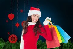 Donna sorridente che tiene i suoi sacchetti della spesa contro il fondo digitalmente generato di natale immagini stock