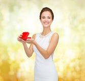 Donna sorridente che tiene il contenitore di regalo rosso Fotografia Stock