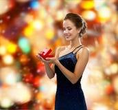 Donna sorridente che tiene il contenitore di regalo rosso Immagini Stock