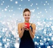 Donna sorridente che tiene il contenitore di regalo rosso Immagine Stock