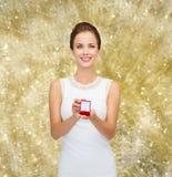 Donna sorridente che tiene il contenitore di regalo rosso con l'anello Immagine Stock