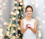 Donna sorridente che tiene il contenitore di regalo rosso con l'anello Immagine Stock Libera da Diritti