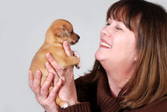 Donna sorridente che tiene piccolo cucciolo Fotografie Stock