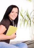 Donna sorridente che tiene un libro Immagine Stock