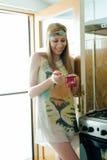 Donna sorridente che tiene una caffettiera in sue mani Immagini Stock Libere da Diritti