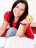 Donna sorridente che tiene una mela e uno studyi Immagini Stock