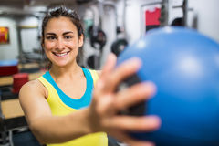 Donna sorridente che tiene una palla medica Immagine Stock