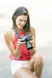 Donna sorridente che usando la sua macchina fotografica di fotografia. Fotografia Stock Libera da Diritti