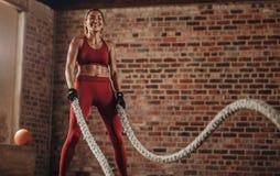 Donna sorridente che usando le corde di battaglia per esercitarsi fotografia stock libera da diritti
