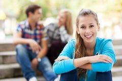 Donna sorridente con gli amici nella priorità bassa Fotografia Stock