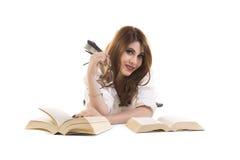 Donna sorridente con i libri che si trovano sul pavimento Immagini Stock