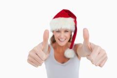 Donna sorridente con i pollici su e un cappello di Natale Fotografia Stock