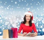 Donna sorridente con i sacchetti della spesa ed il pc della compressa Immagine Stock