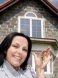 Donna sorridente con i tasti alla casa Fotografie Stock
