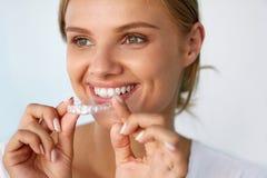 Donna sorridente con il bello sorriso facendo uso dei denti che imbianca vassoio fotografia stock libera da diritti