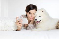 Donna sorridente con il cane di animale domestico Selfie fotografia stock