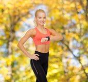 Donna sorridente con il cardiofrequenzimetro a disposizione Fotografia Stock Libera da Diritti
