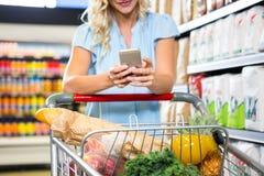Donna sorridente con il carretto facendo uso dello smartphone Immagine Stock