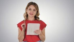 Donna sorridente con il computer della compressa che presenta le pagine di giro sul fondo di pendenza fotografie stock