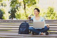 Donna sorridente con il computer portatile all'aperto Fotografia Stock Libera da Diritti