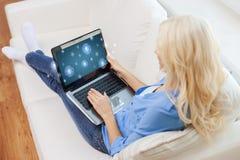 Donna sorridente con il computer portatile a casa Fotografia Stock Libera da Diritti