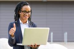 Donna sorridente con il computer portatile che dà pollice su Immagini Stock Libere da Diritti