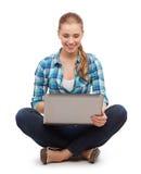 Donna sorridente con il computer portatile che si siede sul pavimento Fotografia Stock Libera da Diritti