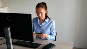 Donna sorridente con il computer portatile e la carta di credito a casa Ragazza con il computer portatile e la carta assegni all' video d archivio