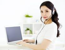 Donna sorridente con il computer portatile e la cuffia Fotografia Stock