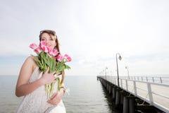 Donna sorridente con il mazzo di mare dei fiori fotografia stock libera da diritti