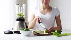 Donna sorridente con il miscelatore che taglia le verdure a pezzi archivi video