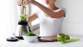 Donna sorridente con il miscelatore e le verdure verdi archivi video