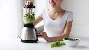 Donna sorridente con il miscelatore e le verdure verdi stock footage