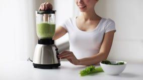 Donna sorridente con il miscelatore e le verdure verdi video d archivio