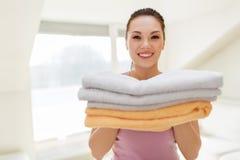 Donna sorridente con il mucchio degli asciugamani di bagno a casa Immagine Stock