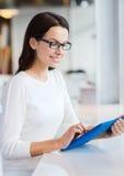 Donna sorridente con il pc della compressa al caffè Immagini Stock