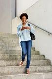 Donna sorridente con il telefono cellulare che cammina giù i punti Fotografie Stock Libere da Diritti