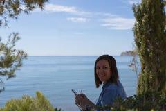 Donna sorridente con il telefono cellulare che guarda overshoulder Fotografia Stock Libera da Diritti