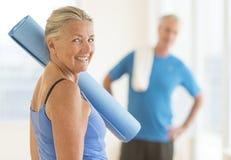Donna sorridente con l'esercizio Mat At Home Fotografia Stock